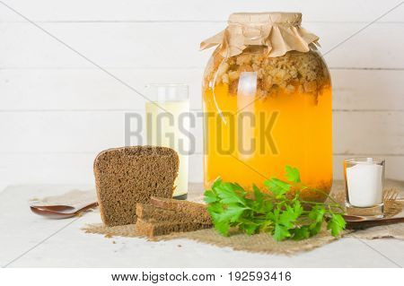 A Large Jar With Kvass Cooking. Black Bread And A Glass With A Drink.