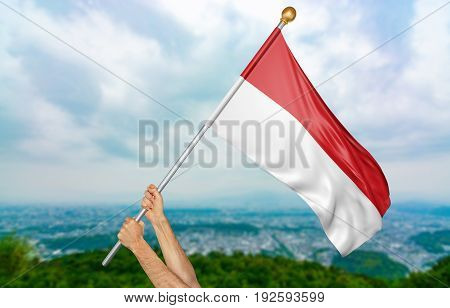 Young man's hands proudly waving the Indonesia national flag in the sky, part 3D rendering