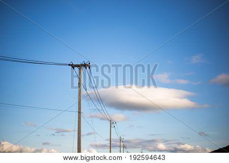Concrete electric pylon power pole under blue sky