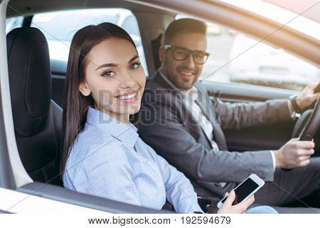 Man and woman transportation by modern eco car holding smartphone