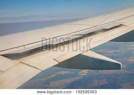 Airplane Wing With The Spoiler Open On The Sky Over Land