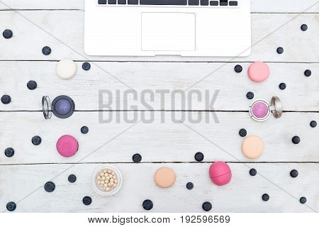 macarons and eye shadow on a white wooden background