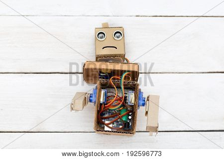 dismantled robot with hands on white wooden background. flat lay