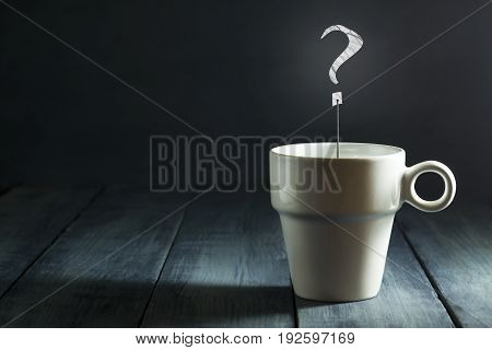 Cup with a question mark on a dark blue background. Business. Concept. With copy space.