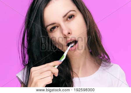 Brunette, woman on a pink background, cleanliness, hygiene, dentistry, toothbrush, a girl brushes teeth.