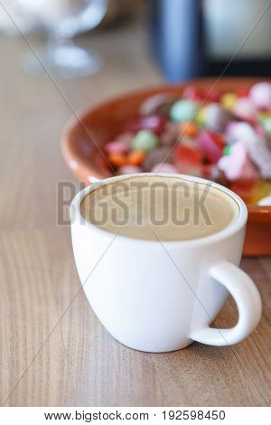 Cup of hot coffee and candies on wooden table