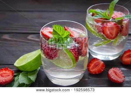 Cold summer drinks in glasses with strawberry , lime and mint