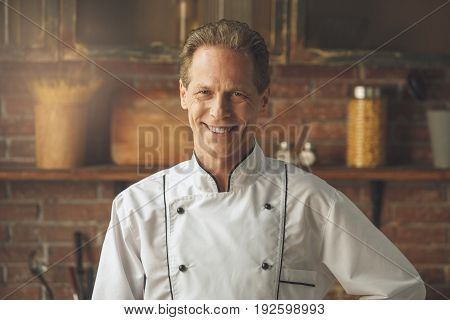 Mature male professional chef cooking meal indoors