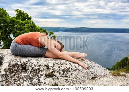 Young woman doing complex yoga exercise on a rock above beautiful river. Sportive woman in the t-shirt, leggings and barefoot. Summer landscape with sky, clouds, tree and river like a background. Concept of the healthy and active lifestyle.