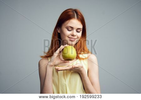Diet, fruit, girl holding an apple on a gray background, beautiful young woman with red hair.