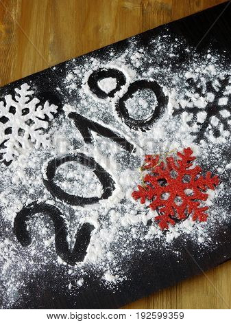 New Year composition on a wooden board covered with flour. Numbers are written with flour