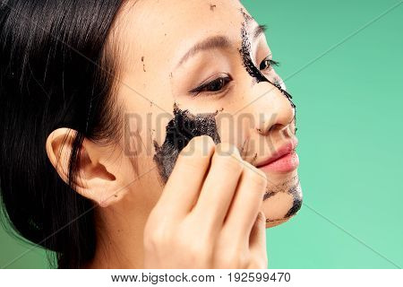 Asian, black coal cosmetic face mask, beauty, health, woman on a green background.