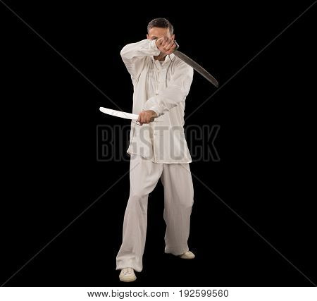 Man in white spining swords on a black backgrownd.