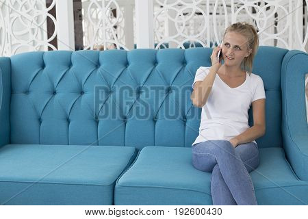 Young beautiful woman sitting on blue modern sofa and talking on mobile phone