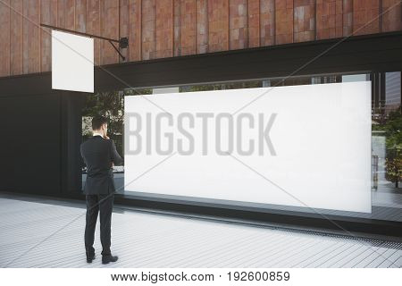 Thoughtful businessman looking at shop window with billboard and stopper. Advertisement concept. Mock up 3D Rendering