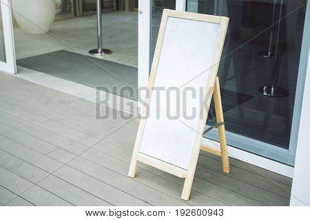 Close up of empty white menu board on cafe verandah. Mock up