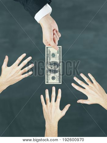 Businessman passing dollar banknotes to hand on chalkboard background. Wages concept