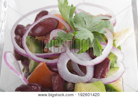 Vegetable salad with red beans in a square glass bowl.  Photo can be used as a whole background.