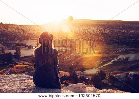 A tourist girl in a hat sits on a mountain and looks at the sunrise and balloons in Cappadocia. Tourism, Turkey.