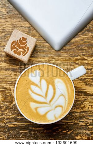 Latte foam, top view. Wooden cube with flower image. Coffee art for beginners.