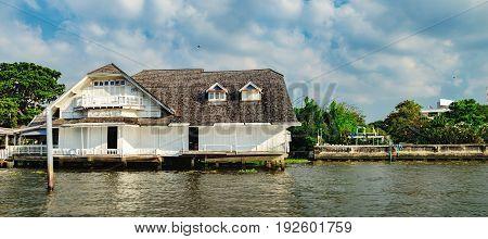 Panorama of Old Chao Phraya River. Thai traditional house village riverfront in Bangkok, Thailand.