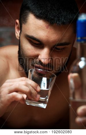 Closeup of young drunken man with bottle and glass sitting in the kitchen at home. Alcohol abuse.