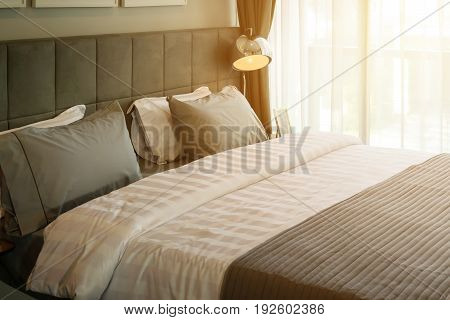Morning Scene In Bedroom With Metal Desk Lamp And Grey Pillow On Bed