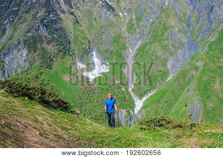 Man Traveler Ascends The Green Slope, In A Mountain Gorge