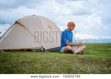 Engaged Traveler Sits Next To The Tent, In The Mountains Using A Tablet