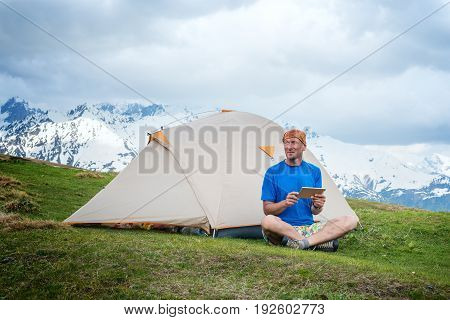Smiling Traveler Sits Next To The Tent, In The Mountains Using A Tablet