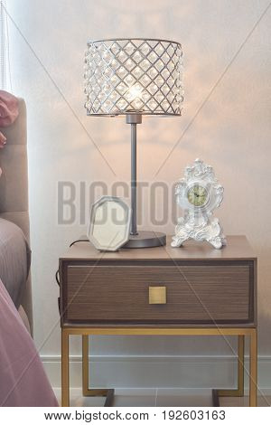 crystal reading lamp and classic alarm clock in cozy bedroom