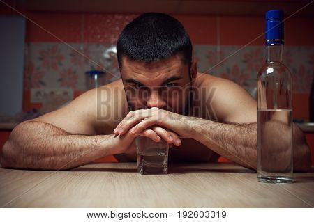 Young man having troubles with alcohol. Male drunk adult sitting at the table with glass and bottle of vodka.