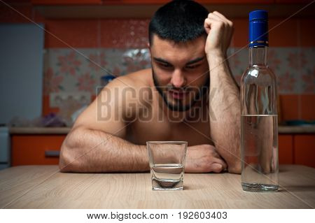 Portrait of young drunken man with bottle and glass sitting in the kitchen at home. Alcohol abuse.