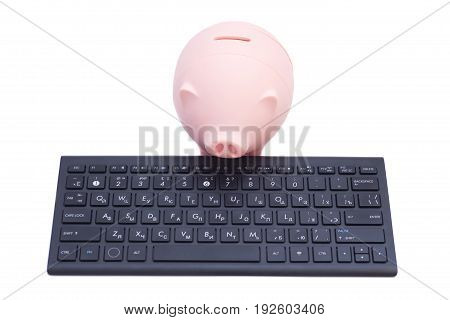Pink piggy bank on black keyboard isolated on white