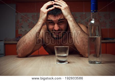 Angry depressed alcoholic man sitting at the table at home. Male adult having troubles with alcohol.