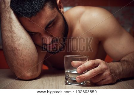 Closeup of drunken man sleeping at the table with glass of alcohol. Addiction concept.