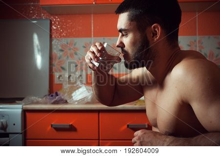 Portrait of young depressed man drinking alcohol at home. Alcohol addiction.