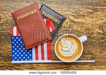 Coffee, passports and American flag. Cup of latte with foam. Starting business in US.