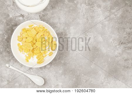 Cup of cornflakes with milk on a light background. Top view copy space. Food background. Toning