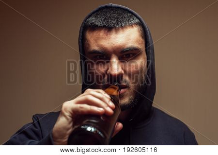 Portrait of young depressed man drinking beer. Alcohol addiction