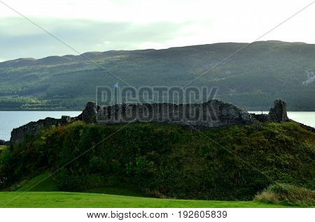 Flag of Scotland flying over the ruins of Urquhart Castle.