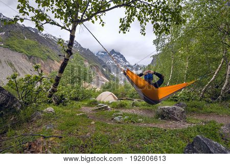 Woman Traveler Relaxing In Hammock In The Mountains