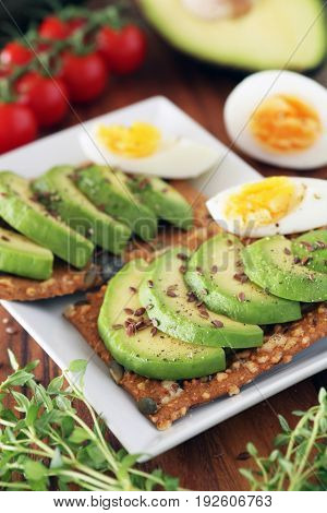 Avocado And Boiled Egg On Pumpkin Seeded Crackers - Shallow Dof