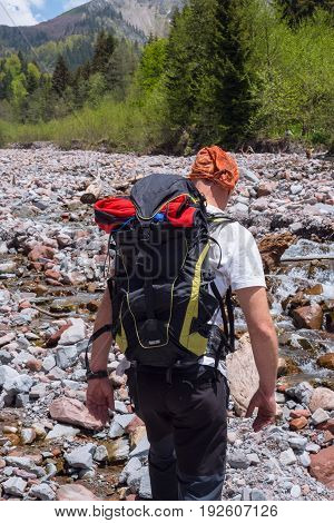 Adventurer With Backpack Crosses A Mountain River