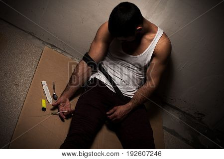 Drug addiction. Overdose young male adult sitting with syringe in hands near wall.