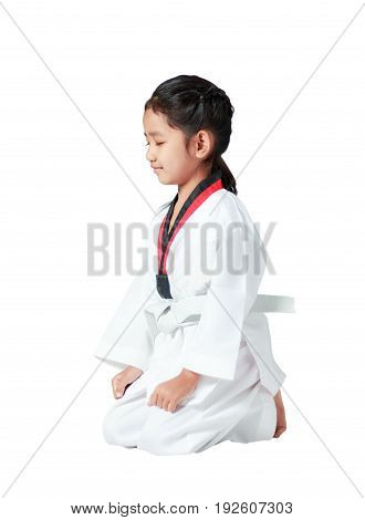 Happy Asian little girl is sitting for concentration in taekwondo uniform isolated on white background with clipping path