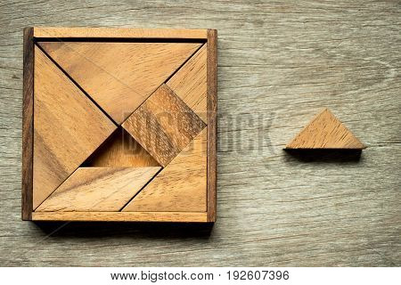 Tangram puzzle in square shape with box wait for fulfillment with one triangle piece on wooden background