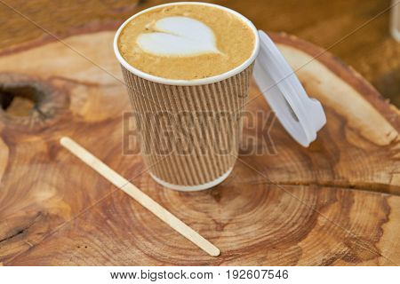 Paper cup with latte. Coffee on wooden board.