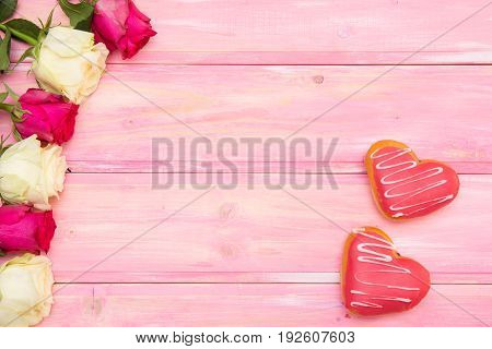 hearts donuts and roses on the wood background