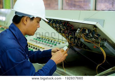 Engineer checking and repairing the electrical system in the control room